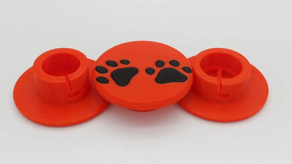 Orange PLA+ caps with black dog print apple emoji